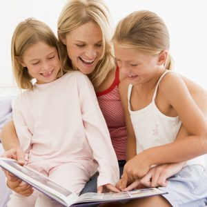 Woman and two young girls in bedroom reading book and smiling